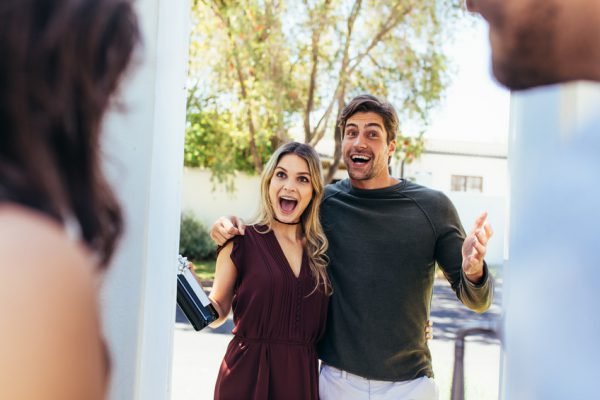 Excited couple at entrance door with bottle of wine. Friends being welcomed by couple at the door. Attending friend's housewarming party.